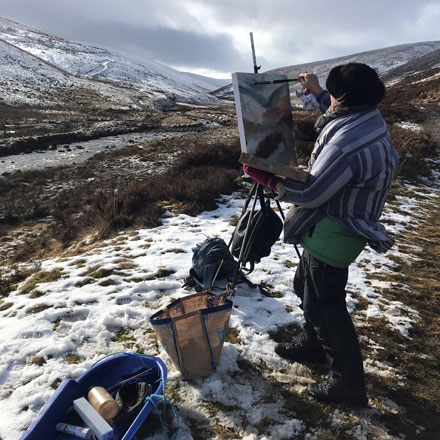 Photo: Gina Farncombe painting out on the Cumbrian Fells.